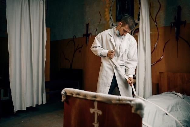 Psychiatra przywiązuje do łóżka szaloną pacjentkę ze szpitala psychiatrycznego. kobieta w trakcie leczenia w poradni dla chorych psychicznie