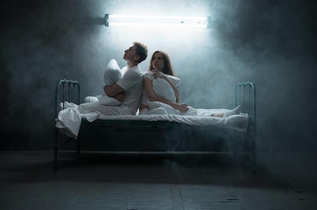 Psychodeliczny mężczyzna i kobieta siedzą w łóżku, w ciemni .. psychodelik ma problemy każdej nocy, depresja i stres, smutek, szpital psychiatryczny