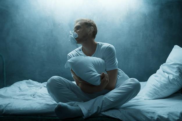 Psychodeliczny mężczyzna przytula poduszkę w łóżku, horror bezsenności, ciemny pokój .. psychodeliczny mężczyzna mający problemy każdej nocy, depresja i stres, smutek, szpital psychiatryczny