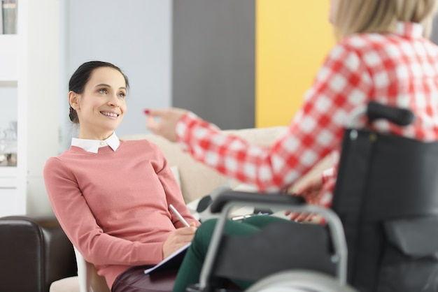 Psycholog kobieta konsultuje się z niepełnosprawną kobietą w koncepcji wsparcia socjopsychologicznego na krześle