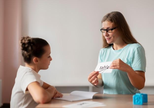 Psycholog pomaga małej dziewczynce w logopedii