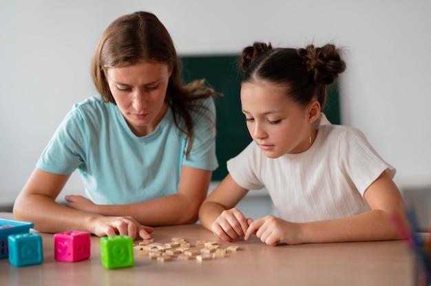 Psycholog pomaga małej dziewczynce w terapii mowy w pomieszczeniu