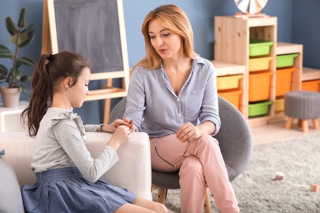 Psycholog pracujący z małą dziewczynką w pomieszczeniu
