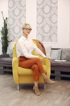 Psycholog siedzi na krześle przy biurem w szkłach