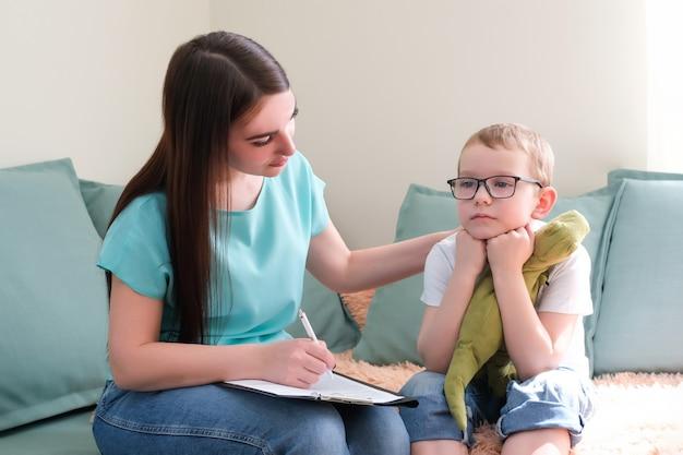 Psycholog słucha małego dziecka podczas sesji terapeutycznej. przedszkolak czuje się swobodnie w gabinecie terapeuty, dzieli się swoimi przemyśleniami i problemami