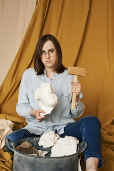 Psychologia choroba psychiczna depresja ból głowy kobieta trzyma gipsową głowę i drewniany młotek