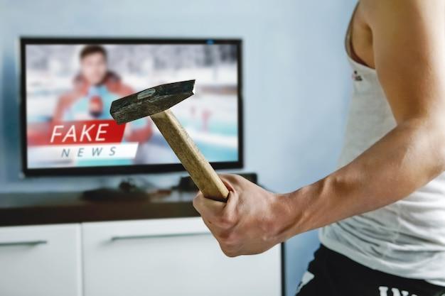 Psychopata chce rozbić telewizor młotkiem. widzowie zmęczyli się fałszywymi wiadomościami. prawda fałszywie przedstawiona w wiadomościach w nowoczesnym telewizorze. fałszywy raport informacyjny. telewizja zombie. oszukiwanie widzów.