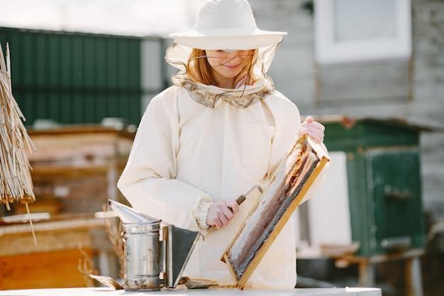 Pszczelarz kobieta opiekuje się pszczołami. noszenie kombinezonu kobieta pracuje w pasiece.