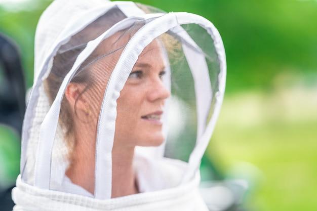 Pszczelarz kobieta w kombinezonie ochronnym w pszczelarstwie
