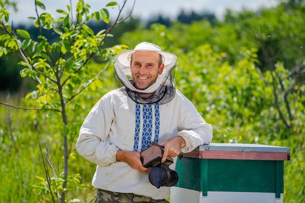 Pszczelarz w ochronnej odzieży roboczej. tło uli w pasiece. pracuje na pasiekach na wiosnę.