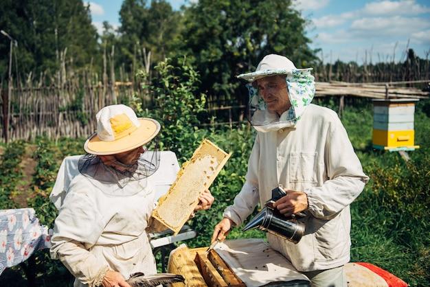 Pszczelarze w pobliżu ula, aby zapewnić zdrowie kolonii pszczół lub zbiorów miodu.