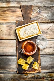 Pszczoła miód na starej desce. na drewnianej powierzchni.