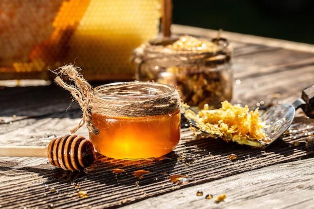 Pszczoła miodna i plaster miodu z czerpakiem miodu na drewnianym stole
