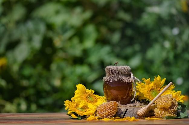 Pszczoła siedzi na szklance miodu
