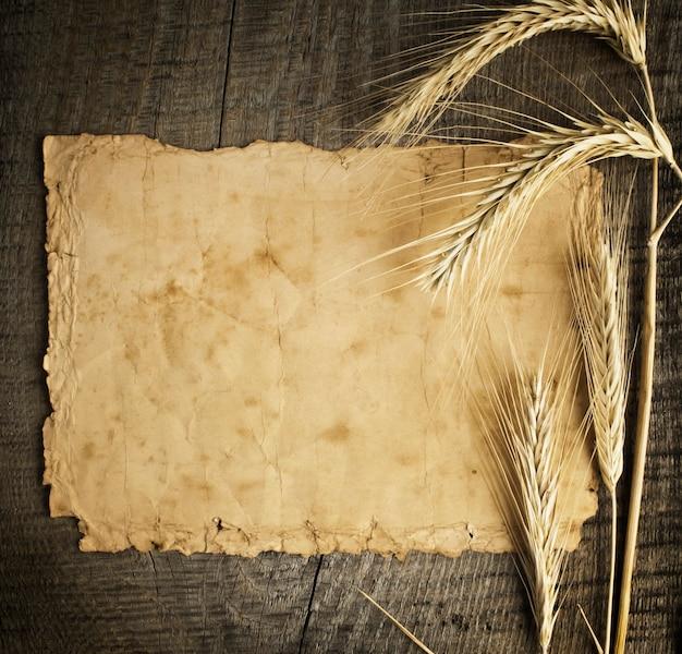 Pszenica na starym drewnianym stole i starym papierze