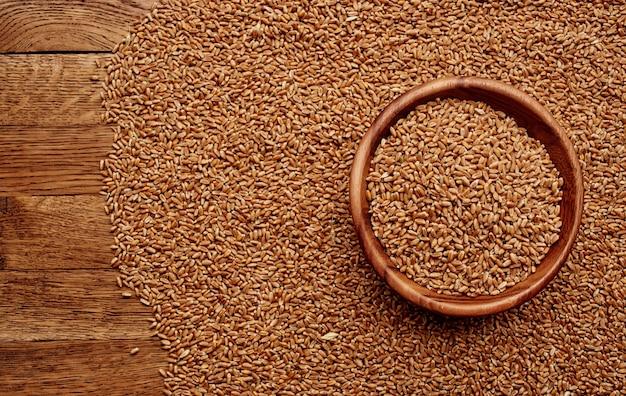 Pszenica posypana na drewnianym stole przygotowanie żywności zbożowej tekstury.