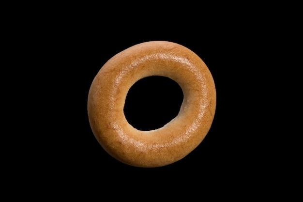 Pszenny bochenek ciasta parzonego w formie pierścienia. bajgiel na białym tle na czarnym tle. zdjęcie wysokiej jakości