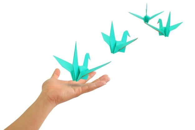 Ptak origami latający z rąk ludzi na białym tle. koncepcja wolności