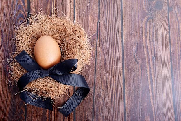 Ptasie gniazdo z jajkiem i czarną wstążką na podłoże drewniane