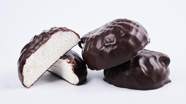 Ptasie mleczko w polewie czekoladowej z bliska na białym tle, ścieżka przycinająca