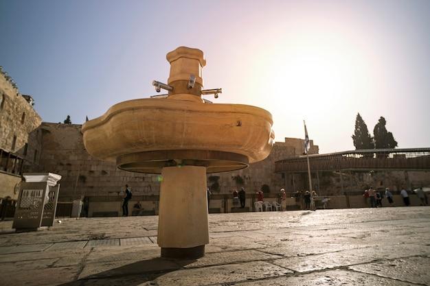 Publiczne złote kubki do rytuału mycia rąk przy ścianie płaczu znajdującej się na starym mieście w jerozolimie u podnóża zachodniej strony wzgórza świątynnego w izraelu.