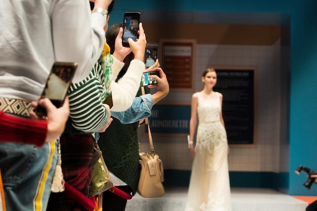 Publiczność korzysta ze smartfona i robi zdjęcia z pokazu mody