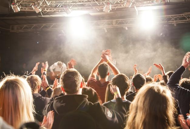 Publiczność oklaskiwała artystę scenicznego. świecą w centrum uwagi.