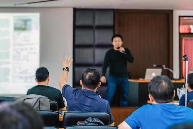 Publiczność pokazuje rękę, aby odpowiedzieć na pytanie mówcy na scenie
