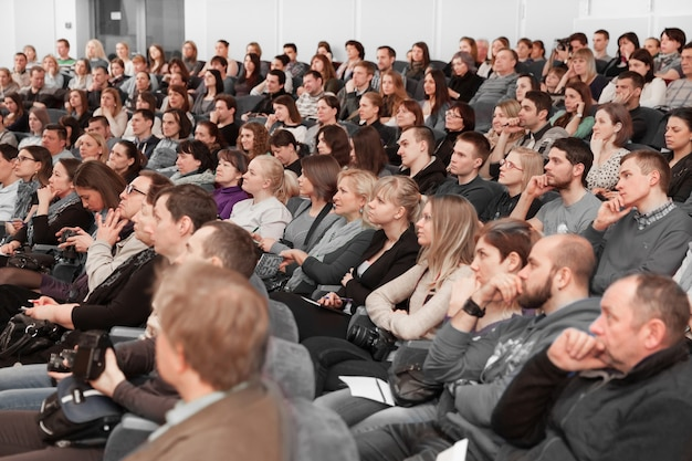 Publiczność siedząca na konferencji prasowej w nowoczesnej sali konferencyjnej