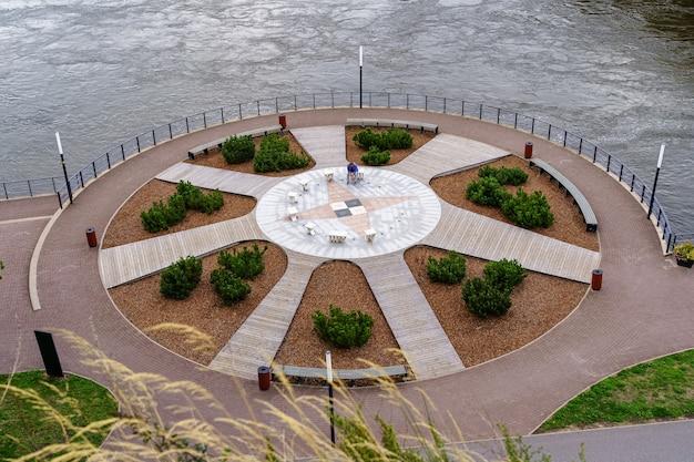 Publiczny park nad rzeką z ozdobnymi roślinami i ławkami do siedzenia.