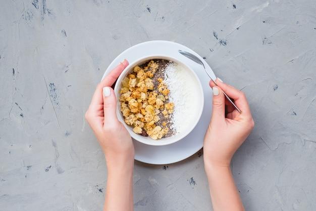 Puchar domowej roboty granola z jogurtem i chia ziarnami na kamiennym tle od odgórnego widoku