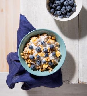 Puchar granola z jogurtem i czarnymi jagodami na białym drewnianym tle