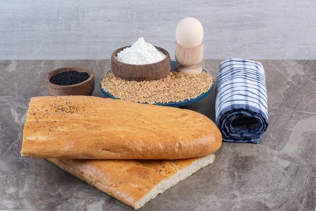 Puchar jaj, miska mąki i stos pszenicy na talerzu obok miski czarnego sezamu, rolki ręcznika i bochenków chleba na marmurowym tle. zdjęcie wysokiej jakości