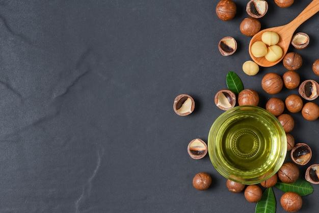 Puchar macadamia dokrętki olej i macadamia dokrętki na czerń kamieniu