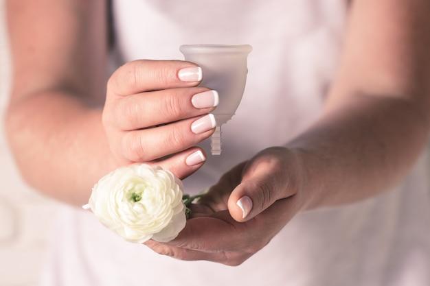 Puchar menstruacyjny w rękach kobiet. kobieta trzyma kwiat i silikonowy kubek higieniczny, nowe urządzenie do minimalizacji odpadów i ochrony środowiska