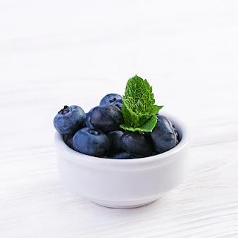 Puchar świeże czarne jagody na białym drewnianym stole. zdrowe jedzenie.