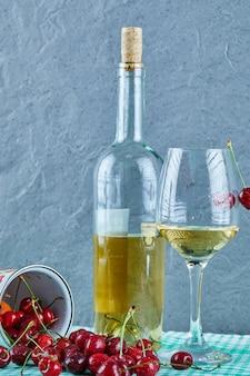 Puchar wiśni, butelka białego wina i szkła na niebieskiej powierzchni