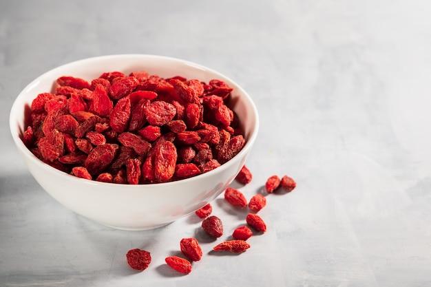Puchar z czerwonymi wysuszonymi goji jagodami na jasnopopielatym tle z kopii przestrzenią.