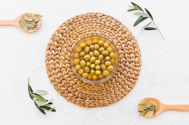 Puchar z oliwkami i olejem i ziele na białym tle