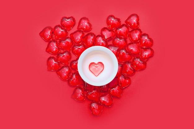 Puchar z sercami na czerwonym tle. widok z góry. wylały się czerwone serca. pojedynczo na różowym tle. skopiuj miejsce