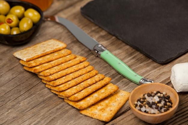 Puchar zielone oliwki, ciastko i nóż na drewnianym stole