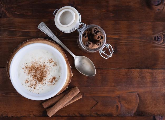 Pudding ryżowy i cynamon na drewnianej podstawie