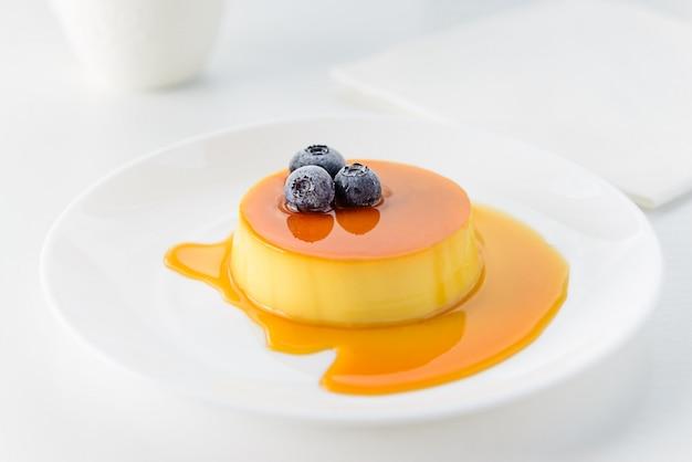 Pudding z jagodami na białym talerzu.