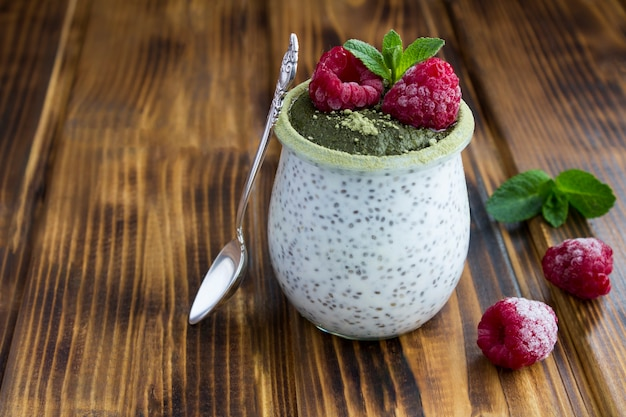 Pudding z nasion chia z malinami i herbatą matcha w szklanym słoju na podłoże drewniane. zbliżenie. skopiuj miejsce.