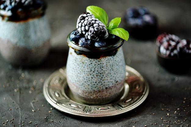 Pudding z nasion chia z miodem, mrożonymi jagodami i jeżynami.