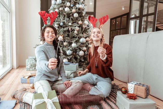 Pudełka dla przyjaciół. wesołe szczęśliwe dziewczyny siedzą na podłodze w salonie i niosą ognie, będąc w świątecznym nastroju. koncepcja bożego narodzenia