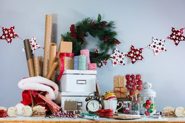 Pudełka do pakowania, prezenty w beżowym papierze pakowym w stylu vintage. wieniec holly berry na tle szarej ściany. koncepcja przygotowania do nowego roku i świąt bożego narodzenia