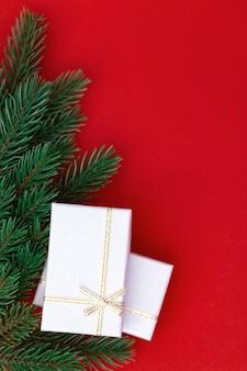 Pudełka do prezentów w kolorze srebrnym na czerwonym tle papieru. boże narodzenie i nowy rok niespodzianka w zamkniętym pudełku z zielonymi gałązkami z choinki.
