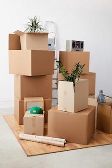 Pudełka kartonowe ułożone w pustym pokoju z roślinami i rzeczami osobistymi w środku, koncepcja przeprowadzki lub relokacji
