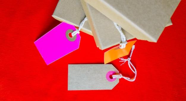 Pudełka kartonowe z metką. brązowe pudełko do pakowania z pustą etykietą i miejscem na kopię na czerwonym tle